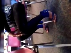Ebony lady with long toenails on sandals.