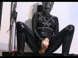 Chick in latex toying her pussy in the dungeon