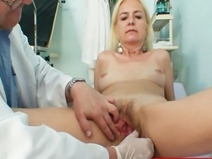 Blond grandma gets her hairy bushy aged vagina opened with a pussy spreader...