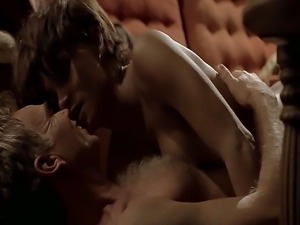 Halle Berry sitting on a couch as a guy pulls up her top to reveal her...