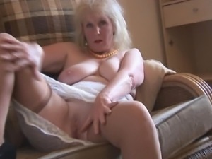 Mature busty lady in stockings and sheer slip strips and teases