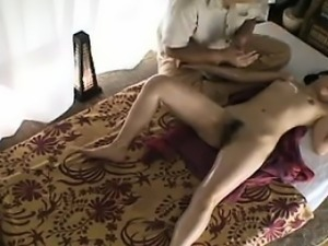 Sultry Oriental girl lies naked on the massage bed and is m